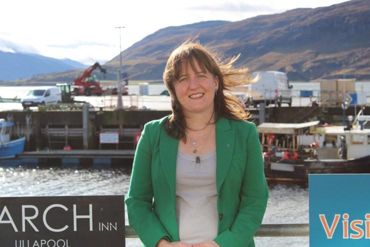Maree Todd standing against railings at Ullapool Harbour