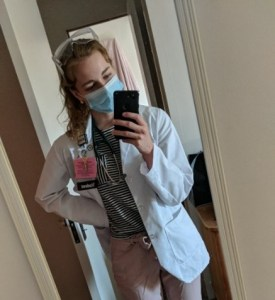 Claire Carmichael taking a photo of herself in her white coat and a mask