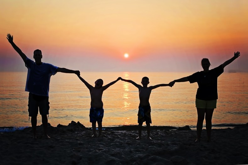 Image of a happy family, jumping for joy, with a kitsch sunset in the background.