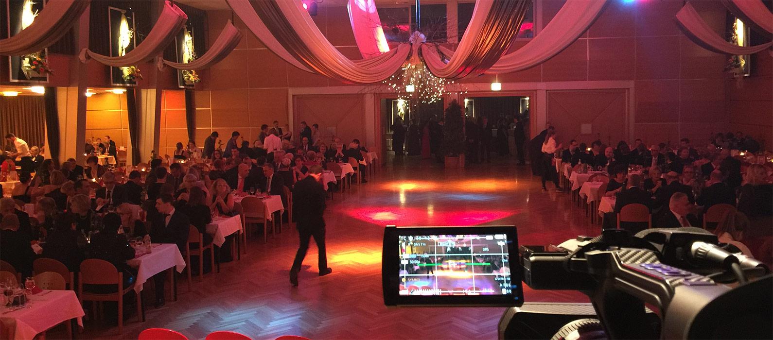 Auf dem Bild ist ein Saal zu sehen, wo offensichtlich gerade ein Ball, eine Hochzeit oder ähnliches stattfindet. Man sieht rechts unten im Bild die Kamera von der alles mitgefilmt wird. Rechts und links sitzen Leute und in der Mitte befindet sich die Tanzfläche.