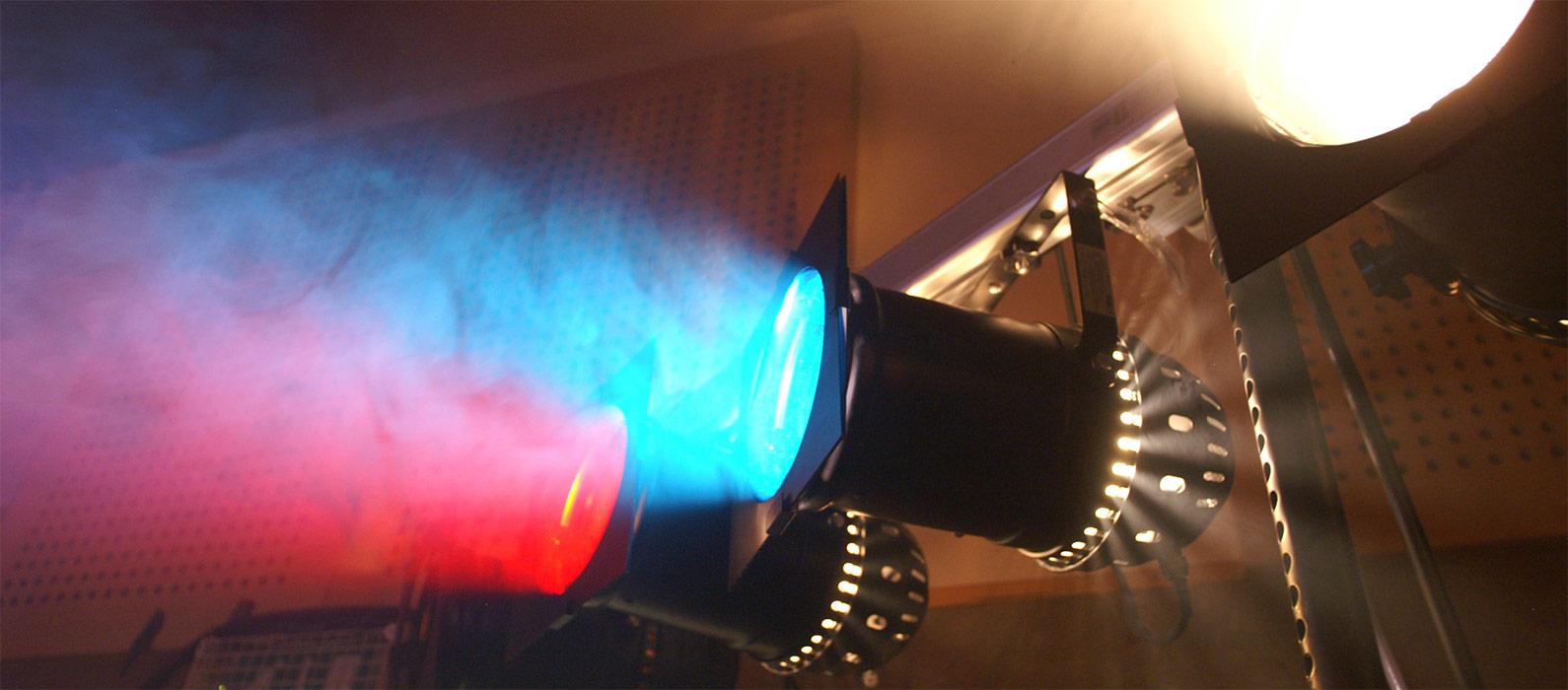 Zwei schwarze Bühnenscheinwerferaus seitlicher Perspektive, die auf einer Stange hängen und schräg nach links oben in einen Nebel leuchten. Der rechte, der eher im Vordergrund ist, leuchtet blau. Der zweite dahinter leuchtet rot.