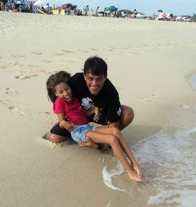 O estudante de psicologia Marcelo Mourão sensibilizando no mar criança especial.