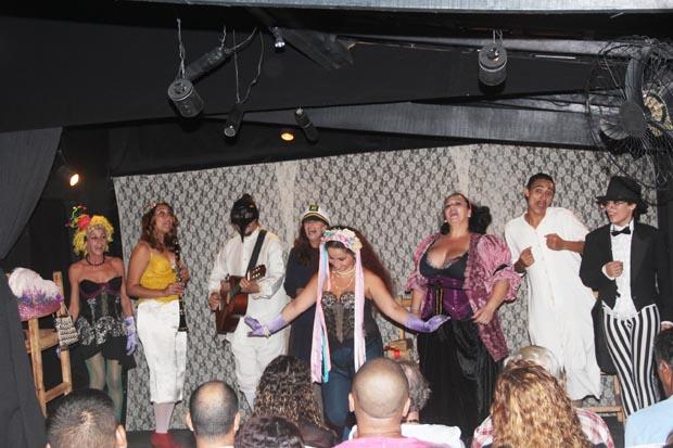 Atores em cena, recebendo o aplauso do público, depois da apresentação de duas peças curtas de Machado de Assis, um clássico da eterna ironia