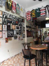 Vista da entrada do Bar do Nei. Itens antigos por todos os lados e cartazes emblemáticos na parede.