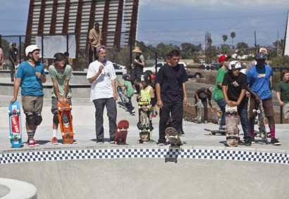 Skaters of all ages wait their turn to drop in.