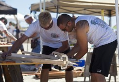 """OPD Harbor Unit officers, Mark Bussey and Jon Hoover build their """"Nail and Sail"""" entry for the Chanchitos de Agua (Water Pig) team."""