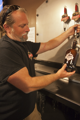"""Legacy Brew Co. co-Owner John """"JJ""""Snyder fills a growler with one of the ales available at the brewery."""