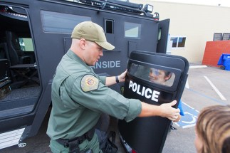 OPD officer, Justin Williams shows Angel, 12, how to hold the shield.