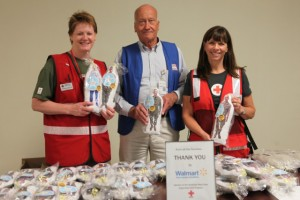 American Red Cross Services to Armed Forces Coordinator Bob Ellison-Peck, was supported at the Camp Pendleton, San Diego, California Hug-A-Hero distribution by Barbara Behling (left) and Mar Tobiason (right)  Photo courtesy of: Virginia Hart, American Red Cross Volunteer