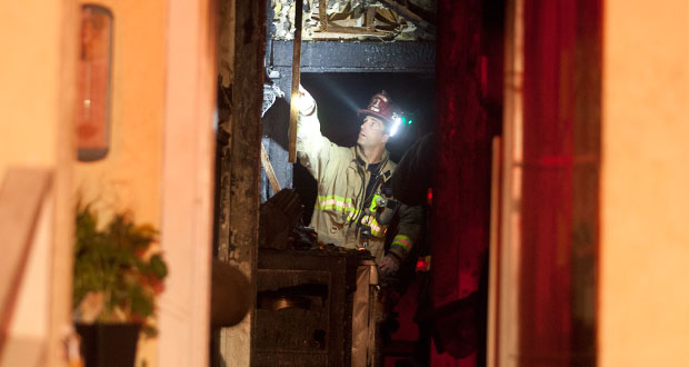 Oceanside Fire Captain Price examines the damage to the home on South Meyers