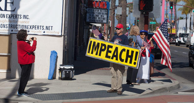 """Dan Russell has his photo taken with his """"Impeach"""" sign"""