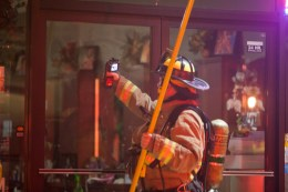 A firefighter uses thermal technology to check for heat at a shop adjacent to Fratelli's