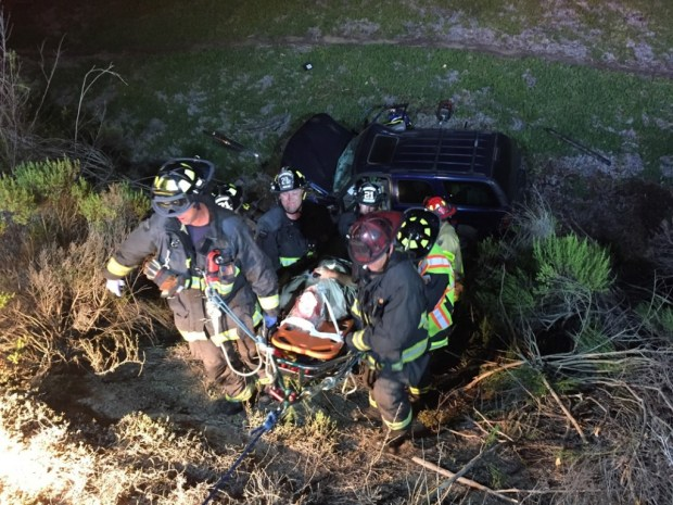 Firefighters bring the victim up to the roadway.(photo: courtesy Oceanside Fire Department)- click on image to enlarge photo