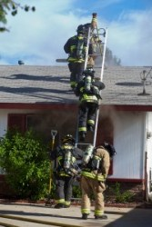 Firefighters make their way to ventilate the roof. (Click on image to enlarge photo)