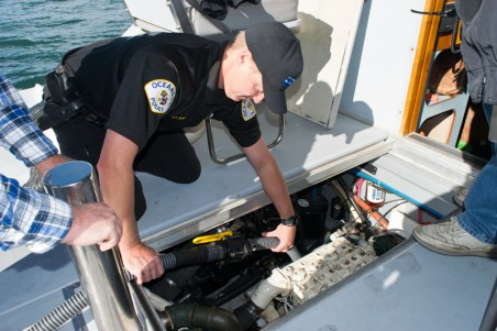 OPD Harbor Division Officer, Mark Bussey demonstrates the pump on the bilge of an OPD boat