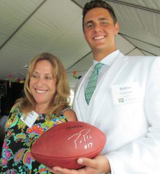 Janet DiPrinzio the winning bidder of this football signed by 5-time NFL Pro Bowl Quarterback Phillip Rivers presented by Scholar Bubba Sugarman.