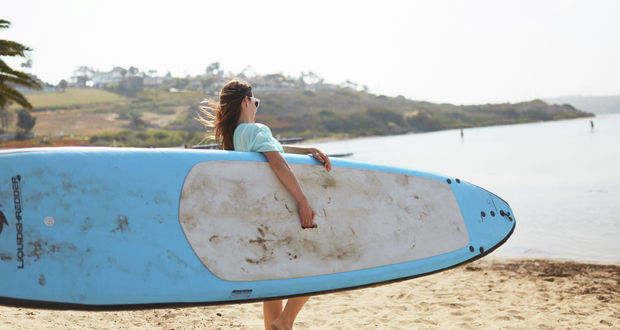 girl carrying paddle board