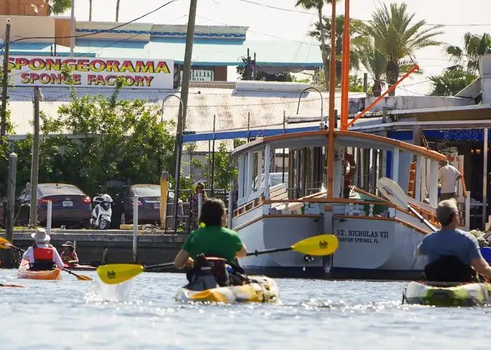 Paddlers on the Anclote River, paddling past sponge boats at the Tarpon Sponge Docks.