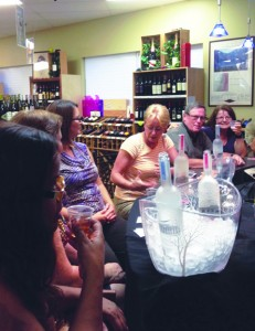 Customers enjoy a taste testing of select liquors.