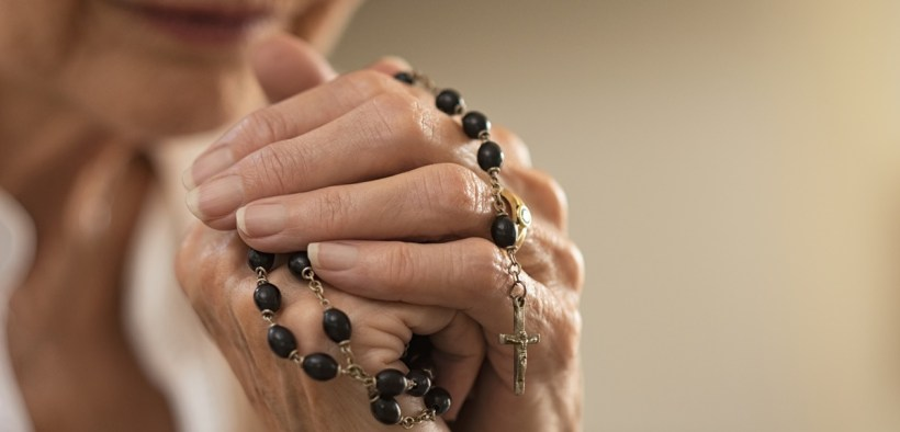 Elderly woman praying rosary