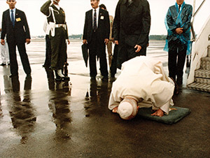 Pope John Paul II kisses rain-soaked tarmac as he arrives in Indonesia in 1989