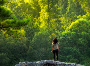 A young female hiker takes a break to enjoy a forest view.