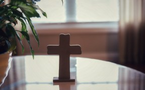 A cross on a glass table-concept bless our home