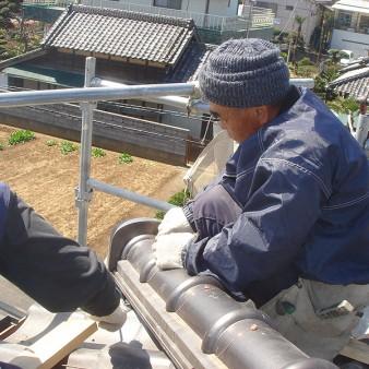 工事中:隅棟の鬼瓦取付、冠瓦を銅線にて固定。