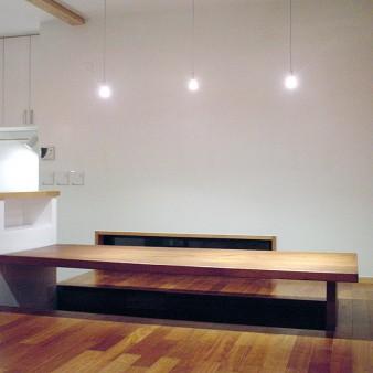 10:居間 テーブルはカランタスの無垢1枚板。足下は掘り炬燵の様に400㎜掘り下げ、床暖房を施している。壁、天井は塗装仕上げ。