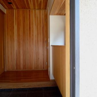 4:玄関 右手に居間、左手に食堂と正面の壁で領域を分けている。壁と天井は杉の無垢板。