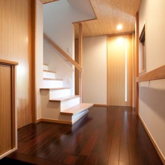 4:玄関 ポーチと玄関が一体の空間になるよう、天井高さは玄関戸に合わせている。 壁は塗装仕上げ、天井は杉の無垢板とし、床は紫檀(ローズウッド)の無垢フローリング。