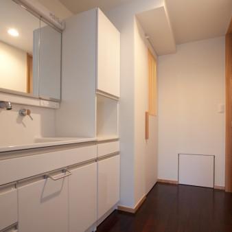 8:洗面所 壁と天井は塗装仕上げとし、床は紫檀(ローズウッド)の無垢フローリング。左手にある格子戸を開けると洗濯機と洗剤等をコンパクトにまとめたスペース。正面の下にある小さな扉はメンテナンス用の点検口。