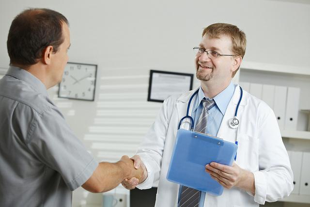 Médecin au comportement non verbal positif avecson patient