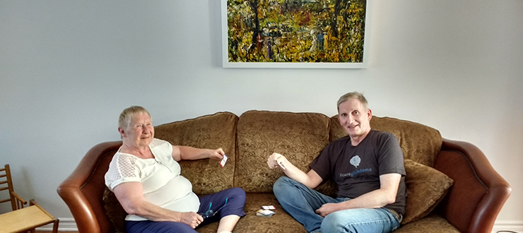 Susan and Ron Wulf sit on a couch playing cards