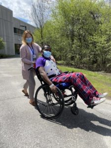 A patient performs a wheelie in a wheelchair supported by physiotherapist Melanie White.