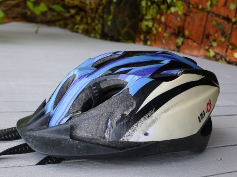 blue and white bicycle helmet that has suffered from an accident