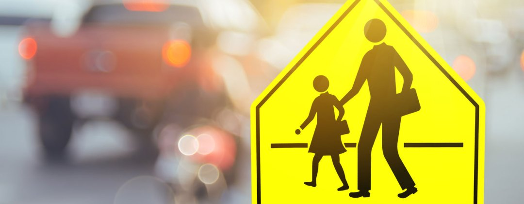 School zone safety sign with blurred traffic in background