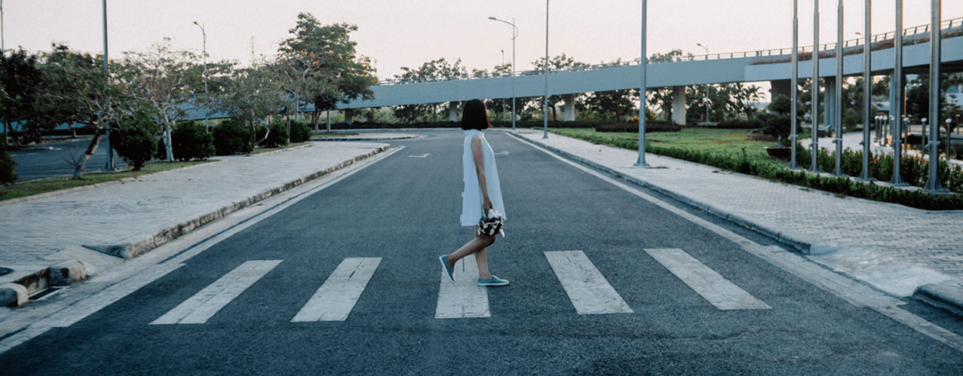 Person walking over a crosswalk looking in the distance