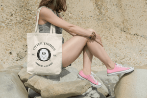 Otter Things 2011 Logo tote bag mockup with young woman sitting on rocks in a sunny day.