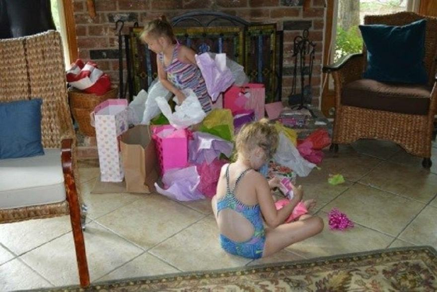 Isabella in front sneakily opening a present from Ellie's 4th Birthday Party