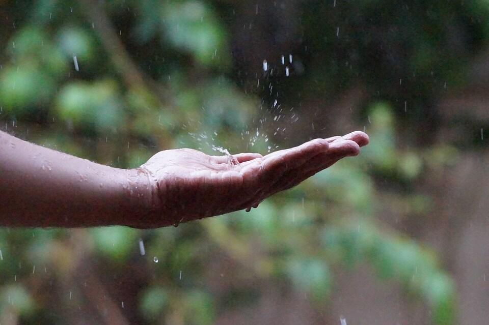 une main avec des gouttes de pluie