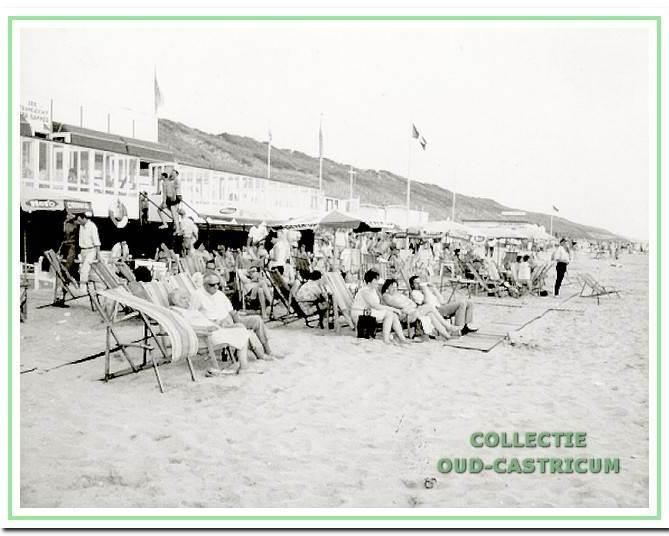 Badgasten in ligstoelen voor strandpaviljoen Bakker.