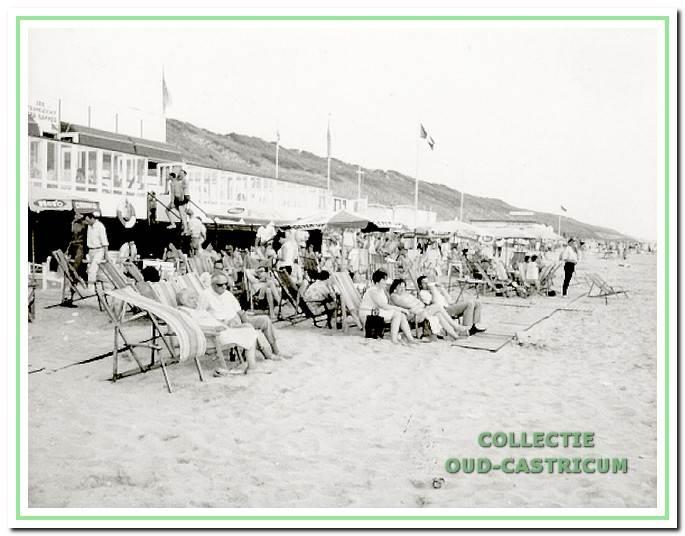 Badgasten in ligstoelen voor het strandpaviljoen van Bakker.