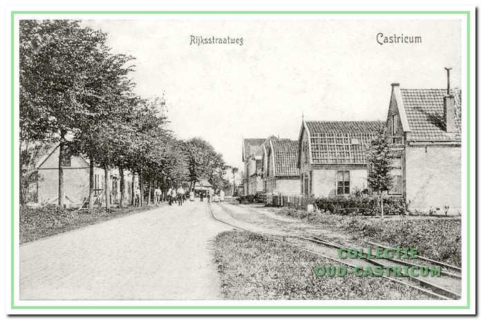 Doorkijk Dorpsstraat in 1910. Aan de linkerkant van de Rijksstraatweg zien we tussen de bomen het pand waarin thans 'Buona Sera' is gevestigd. Een handkar, gestapelde planken tegen de gevel en een aantal personen voor het huis geven een indruk van bouwactiviteiten, al is niet duidelijk waar.