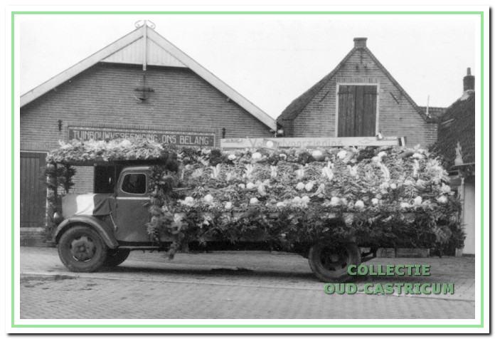 Het oude veilinggebouwtje in 1945. De vrachtwagen van Gerrit Borst is versierd voor de bevrijdingsfeesten.