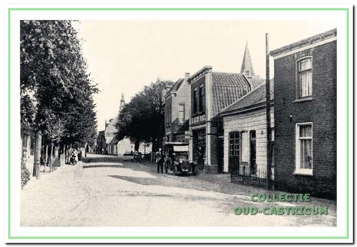 Doorkijk Dorpsstraat omstreeks 1921, met rechts het houten huisje van Siem Schram, ingeklemd tussen de panden die bekend werden als 'De Gezonde Apotheek' van Ytzen Beintema en 'De Nieuwe Winkel' van Jan Stolk. Daarachter nog een glimp van het lage woongedeelte van het oorspronkelijke pand van Jan Stolk en van de twee panden die Cornelis Stolk omstreeks 1911 liet bouwen.