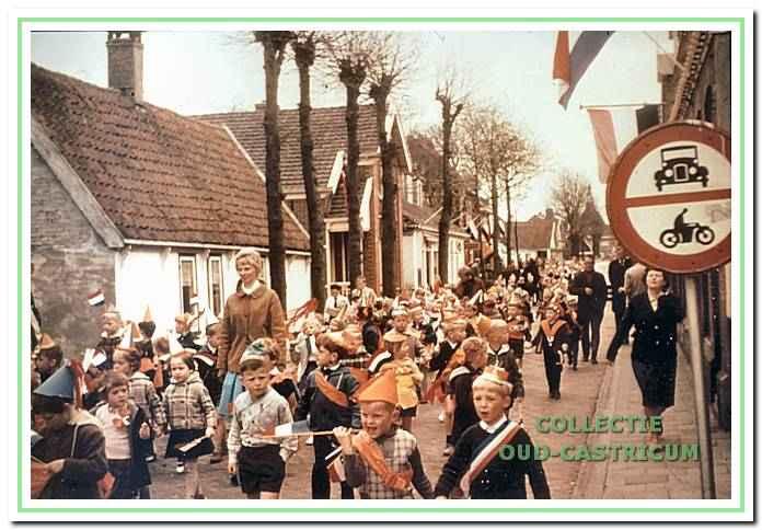 Straatgezicht met kinderen op weg naar de veiling in verband met Koninginnedag.