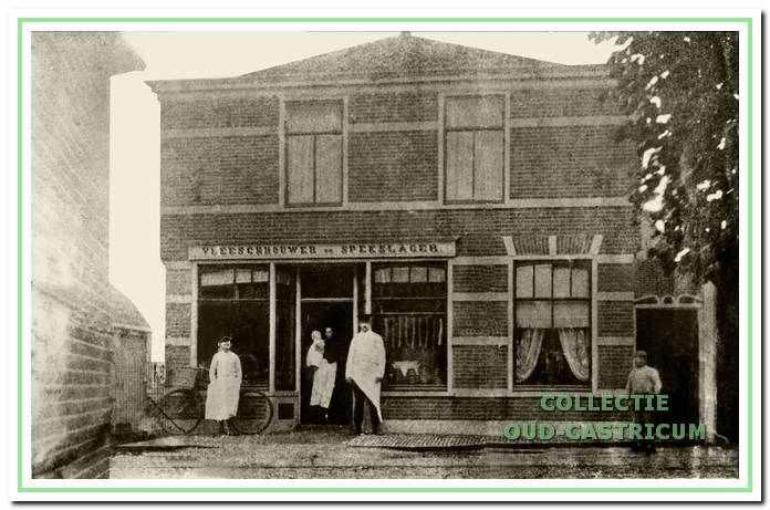 Deze foto uit 1905 toont Hendrik van der Woude voor zijn slagerswinkel met in de deuropening zijn vrouw Wilhelmina van Eck en haar dochtertje Jacoba. Winkelopschrift: Vleeschhouwer en Spekslager.