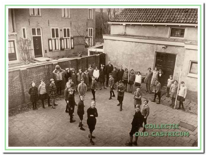 Schoolkinderen en onderwijzers, staande op het schoolplein van de openbare lagere school aan de Dorpsstraat.