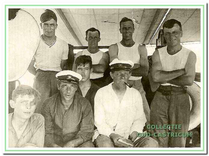 Scheepsjongen Dirk zittend achter de bootsman (met pijp) en andere collega's op het dek van de Blitar.